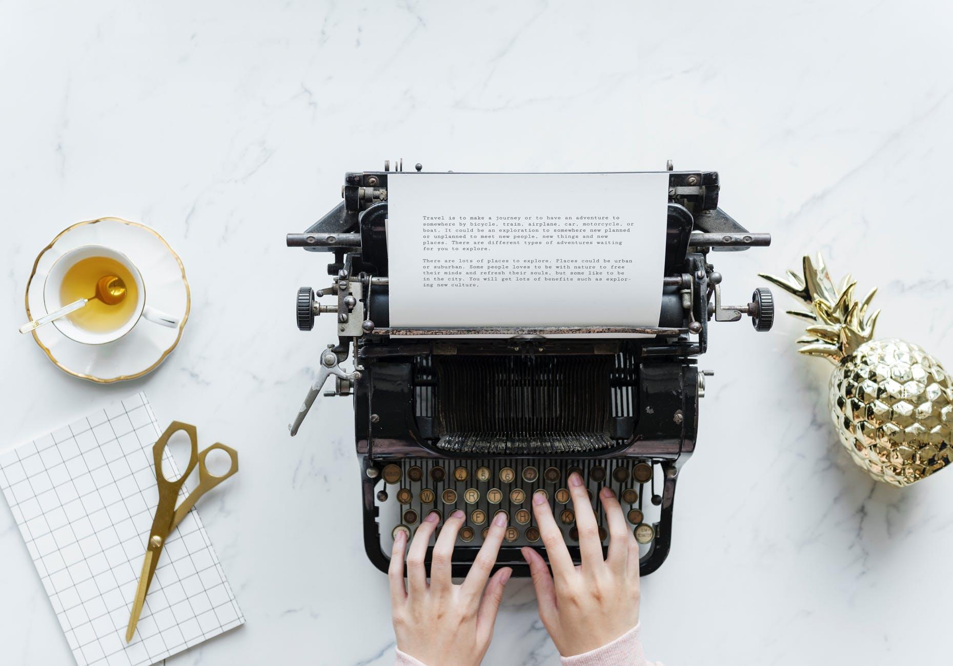 person typing on typewriter